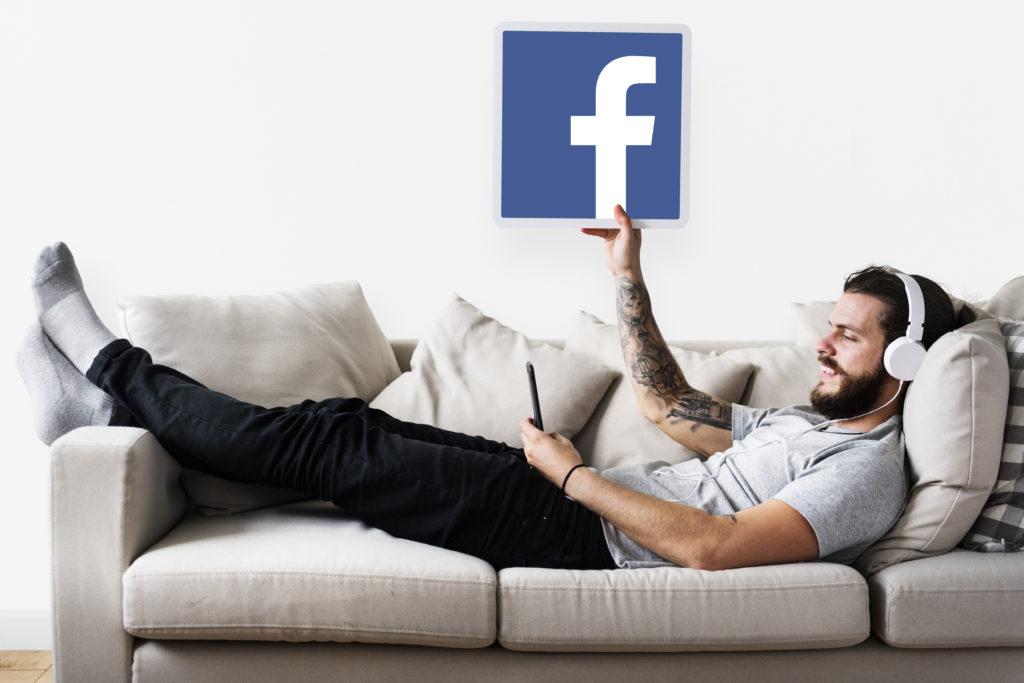 mężczyzna słucha muzyki i wskazuje ikonę facebooka