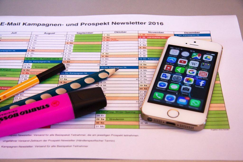 Telefon i pisaki na kartce planu kampanii, określanie grupy docelowej odbiorców na Facebooku