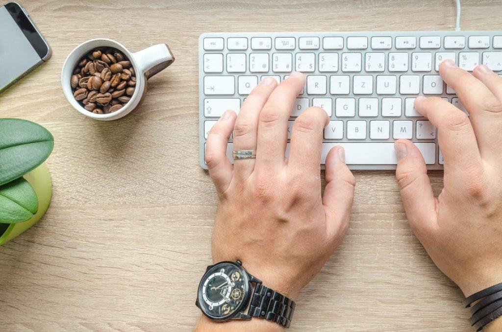 biała klawiatura, kubek z ziarnami kawy